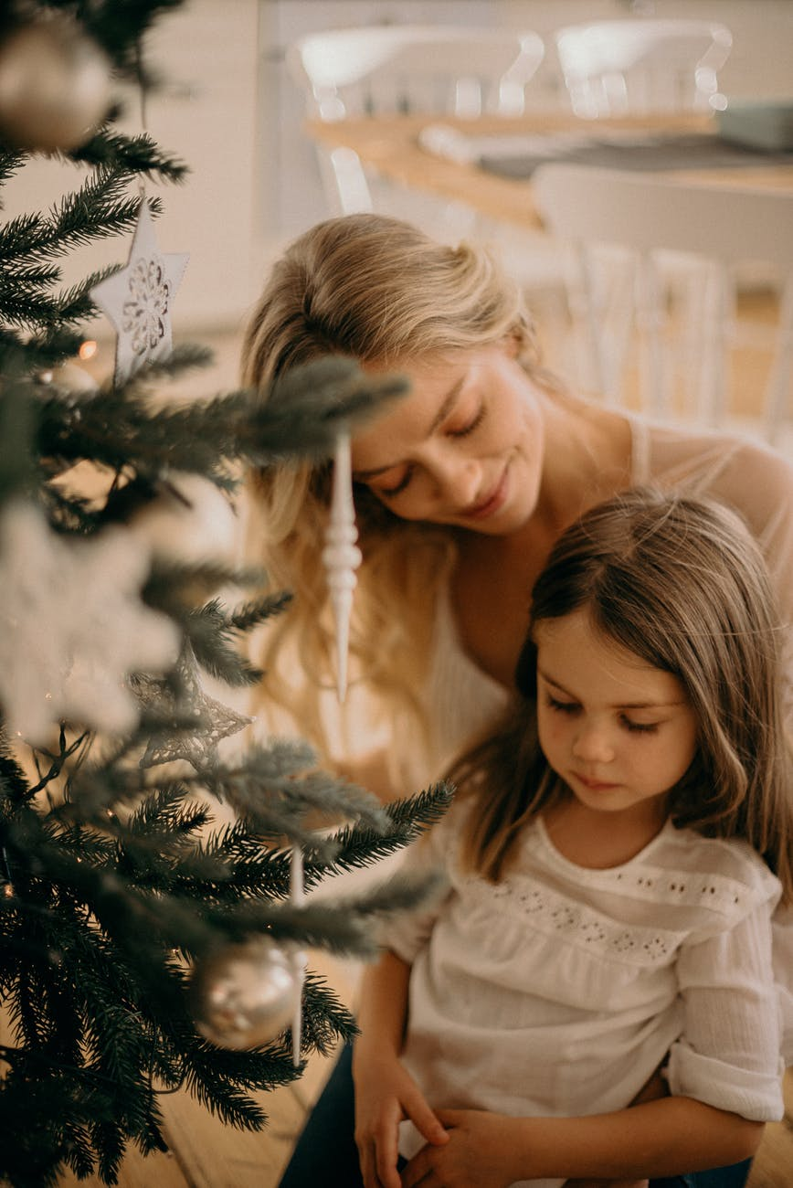 mother and child celebrating family beside Christmas tree